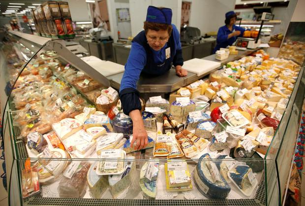 A worker arranges cheese for sale at a grocery store in Moscow
