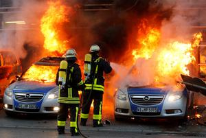 Firefighters extinguish flames in burning police cars that were set afire Wednesday, March 18, 2015 in Frankfurt, Germany. The Blockupy alliance said activists plan to try to blockade the new headquarters of the ECB to protest against government austerity and capitalism.  (AP Photo/Michael Probst)