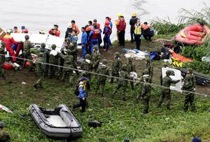 Rescuers and soldiers remove air plane parts after a TransAsia plane crashed into a river in New Taipei City. Reuters/Pichi Chuang