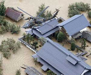 An aerial view shows a local rewsident is rescued by a Japan Self-Defence Force helicopter from residential areas flooded by the Chikuma river, caused by Typhoon Hagibis in Nagano, central Japan, October 13, 2019, in this photo taken by Kyodo Mandatory credit Kyodo/via REUTERS