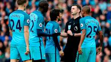 Manchester City players surround referee Michael Oliver after the Liveprool penalty during the Premier League match at the Etihad Stadium