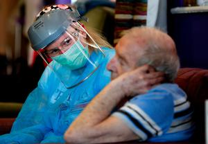 A nurse speaks to a resident at the Wren Hall care home in Nottingham (AP Photo/Frank Augstein)