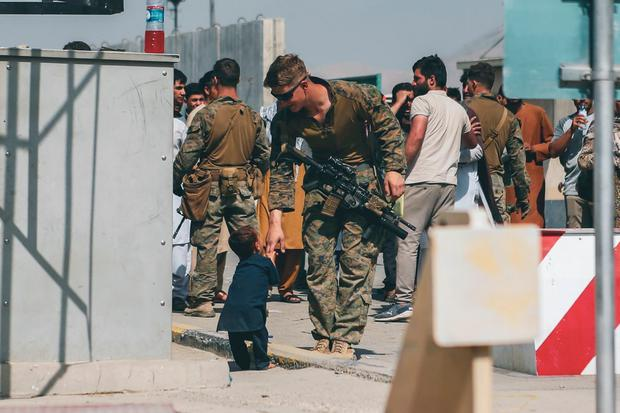 A US Marine plays with a child during an evacuation at Kabul airport