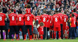 Liverpool players wear Steven Gerrard shirts after the game as they wait for him to be presented to the crowd