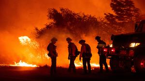Warning: Firefighters monitor the Bear Fire burning in Oroville, California, yesterday. Photo: AP Photo/Noah Berger