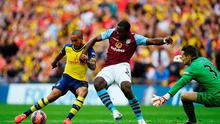 Theo Walcott is foiled by Jores Okore and Shay Given of Aston Villa during the FA Cup Final