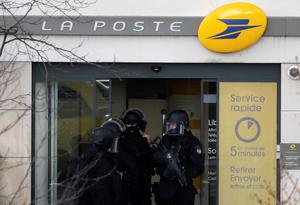 Members of special French RAID forces secure the entrance to the post offices in Colombes outside Paris, were an armed gunman is holding hostages January 16, 2015.    REUTERS/Philippe Wojazer