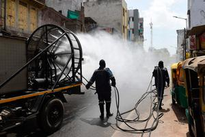 Firefighters from Ahmedabad Fire and Emergency Services spray disinfectant along a street during Gujarat's government-imposed lockdown as a preventive measure against the COVID-19 coronavirus, in Ahmedabad   (Photo by SAM PANTHAKY/AFP via Getty Images)