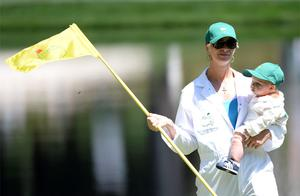 Bubba Watson's wife, Angie Watson, lifts his son, Caleb, during the Par 3 Contest. Photo: Reuters