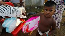 A Rohingya migrant child, who arrived in Indonesia by boat, holds a shark balloon inside a temporary compound for refugees in Kuala Cangkoi village in Lhoksukon, Indonesia's Aceh Province (REUTERS/Beawiharta)