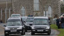 Together: The hearses carry William and Madge Finlay through Ardstraw, Co Tyrone, where the community lined the road – two metres apart. Photo: John McVitty