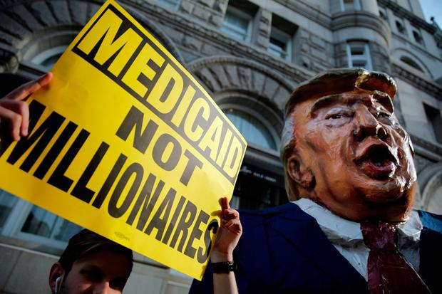 A protester with a puppet of Donald Trump outside Trump International Hotel in Washington. Photo: Reuters