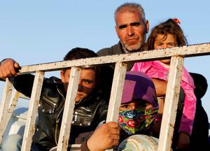 Newly arrived Syrian Kurdish refugees stand at the back of a truck after crossing into Turkey from the Syrian border town Kobani, near the southeastern Turkish town of Suruc in Sanliurfa province. Reuters