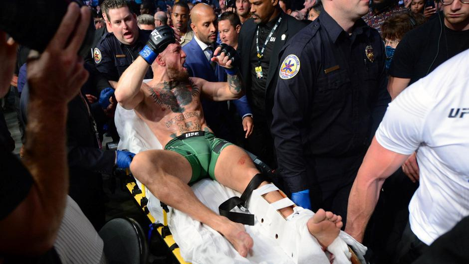 Conor McGregor is carried off on a stretcher following an injury in his loss against Dustin Poirier