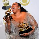 TOPSHOT - US singer-songwriter Lizzo poses in the press room with the awards for Best Pop Solo Performance, Best Urban Contemporary Album and Best Traditional R and B Performance during the 62nd Annual Grammy Awards on January 26, 2020, in Los Angeles. (Photo by FREDERIC J. BROWN / AFP) (Photo by FREDERIC J. BROWN/AFP via Getty Images)