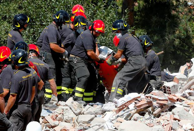 A body is carried away by rescuers following an earthquake in Amatrice, central Italy, August 25, 2016