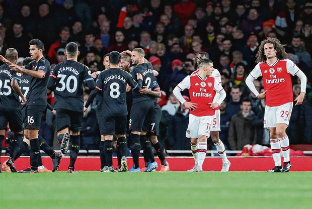 Political football: Arsenal's Lucas Torreira and Matteo Guendouzi (No 29) can't hide their dismay as Manchester City players celebrate their second goal at the Emirates yesterday. Photo: Hannah McKay/Reuters