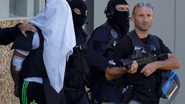 A man supposed to be the suspect who held over an attack against a gas company site is escorted by police officers during investigations in Saint-Priest, near Lyon, France, June 28, 2015.  Yassin Salhi, 35, told detectives he had killed Herve Cornara in a parking area before arriving at the plant in Saint Quentin-Fallavier, 30 km (20 miles) south of Lyon, where he attempted to cause an explosion on Friday, the source told Reuters.  REUTERS/Emmanuel Foudrot