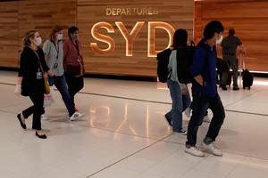 Travellers walk past the departures gate at Sydney International Airport on Wednesday March 25, 2020. Prime Minister Scott Morrison has announced further restrictions on Australians as the government works to stop the spread of Covid-19
