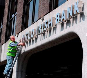 A worker removing the Anglo Irish Bank sign from outside the bank's headquarters in St Stephens Green in 2011