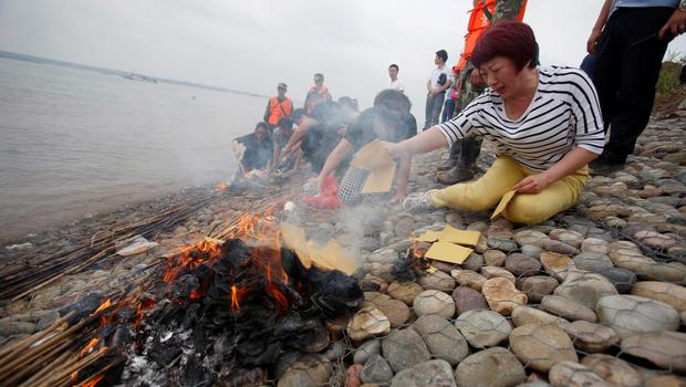 Family members of Eastern Star cruise ship victims burn joss paper as they mourn during a ceremony to mark seven days since the ship went down in the Jianli section of Yangtze River, Hubei province, China, June 7, 2015. REUTERS/Chen Zhuo/Yangzi River Daily