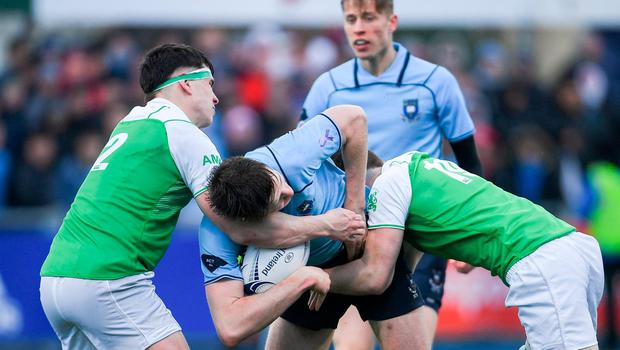 Simon O'Kelly of St Michaels College is tackled by George Kenny, left, and Callum Murphy of Gonzaga College. Photo: Ramsey Cardy/Sportsfile