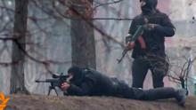 A riot policeman watches as a sniper fires from a fortified position in the direction of protesters. Reuters