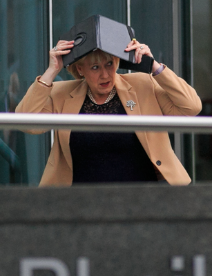 RUNNING FOR COVER: Fine Gael's Heather Humphreys uses her iPad to protect her hair as she arrived at the Convention Centre where Micheal Martin was elected Taoiseach