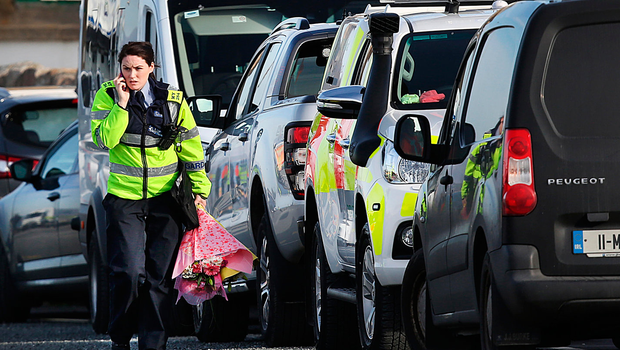 Family liaison officer Garda Sinéad Barrett brings flowers to Blacksod Pier as the search continues for the Rescue 116 crew Photo: Steve Humphreys