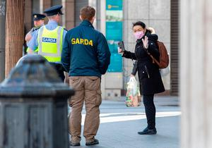Garda talk with members of the public as they conduct checks on pedestrians and motorists in Dublin city centre. (Photo by PAUL FAITH / AFP) (Photo by PAUL FAITH/AFP via Getty Images)