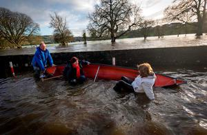The Tanaiste Joan Burton (right) pictured as a boat capsized on the Quays in Thomastown Co. Kilkenny with Ann Phelan TD Minister of State at the Departments of Agriculture, Food and Marine and Transport, Tourism and Sport with Special Responsibility for Rural Economic Development (implementation of the CEDRA Report) and rural transport while being taken to Shem Caulfeilds flooded house. Shem is pulling the boat Picture Dylan Vaughan.