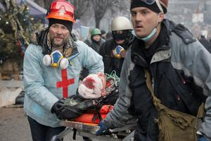 Activists  evacuate a wounded protester during clashes with police in Kiev's Independence Square