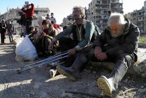 Civilians sit with their belongings as they wait to be evacuated from a besieged area of Homs