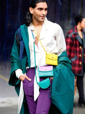 Model Rahi Chadda is seen wearing a teal coat, white shirt, purple pants, several handbags and black boots all by Coach outside of the Coach 1941 show during New York Fashion Week on February 11, 2020 in New York City. (Photo by Donell Woodson/Getty Images)