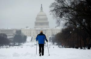 A man skis along the National Mall towards the Capitol in Washington