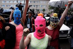 Pussy Riot members Nadezhda Tolokonnikova and Maria Alekhina make their way through a crowd after they were released from a police station