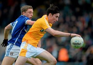 Conor Small under pressure from Cavan's Lewis Fay Cooper