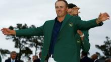 Defending champion Bubba Watson of the U.S. puts the traditional green jacket on compatriot Jordan Spieth after Spieth won the Masters at Augusta