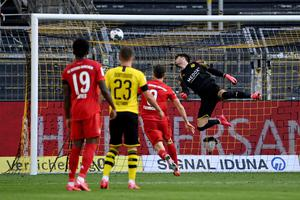 Dortmund's goalkeeper Roman Buerki, right, fails to safe a shot by Munich's Joshua Kimmich during the German Bundesliga soccer match in Dortmund, Germany, on Tuesday evening.