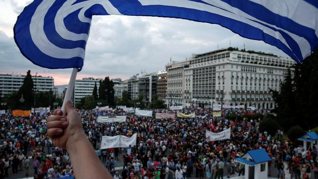 An anti-austerity protester waves a Greek flag during a rally in front of the parliament in Athens