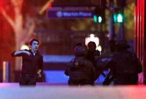 A hostage (L) runs towards police officers near Lindt Cafe, at Martin Place in central Sydney. Reuters/Jason Reed