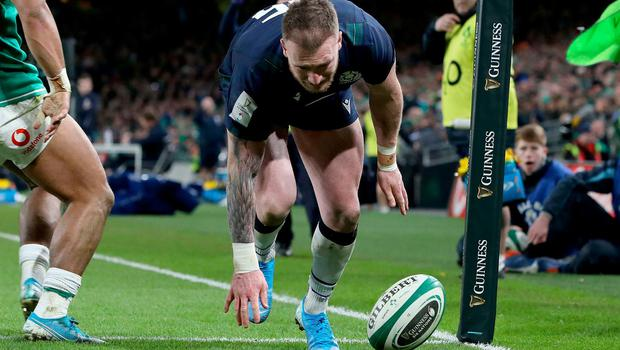 Scotland's full-back Stuart Hogg (C) fumbles the ball and drops it before claiming a try, subsequently denied after a review, during the Six Nations match against Ireland. (Photo by PAUL FAITH/AFP via Getty Images)