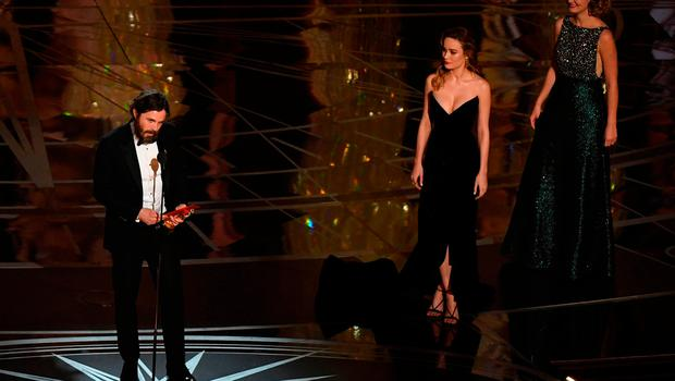 """US actor Casey Affleck (L) delivers a speech on stage next to actress Brie Larson (2ndR) after he won the Best Actor award in """"Manchester By The Sea"""" at the 89th Oscars on February 26, 2017 in Hollywood, California. / AFP PHOTO / Mark RALSTONMARK RALSTON/AFP/Getty Images"""