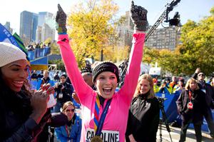 Tennis player Caroline Wozniacki raises her hands after getting a medal for completing the New York City Marathon in New York Sunday, Nov. 2, 2014. Left is tennis player Serena Williams. (AP Photo/Craig Ruttle)