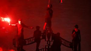 Liverpool fans light flares last night outside Anfield to celebrate their first league win in 30 years. Photo: Reuters