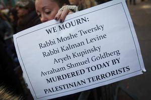 A woman holds a sign during a demonstration against a deadly attack on a Jerusalem synagogue, across the street from the Palestine Mission to the United Nations in New York. Two Palestinian men armed with meat cleavers and a gun entered the synagogue in a quiet ultra-Orthodox neighborhood during morning prayers on Tuesday and attacked around 25 worshippers, killing four and wounding eight, several seriously. Three of the victims held dual U.S.-Israeli citizenship (REUTERS/Carlo Allegri)