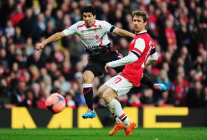 Liverpool's Luis Suarez holds off Arsenal defender Nacho Monreal to get his shot in
