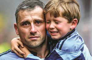 A tearful Alan Brogan of Dublin leaves the pitch with his son Jamie after defeat by Donegal in 2014