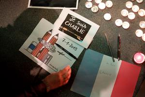 A woman places a drawing and a pen at a makeshift memorial outside the Consulate General of France during a vigil to pay tribute to the victims of an attack on satirical magazine Charlie Hebdo in Paris, in San Francisco, California January 7, 2015.  REUTERS/Stephen Lam