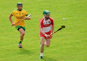 Derry's Brendan Quigley charges forward, pursued closely by Danny Cullen